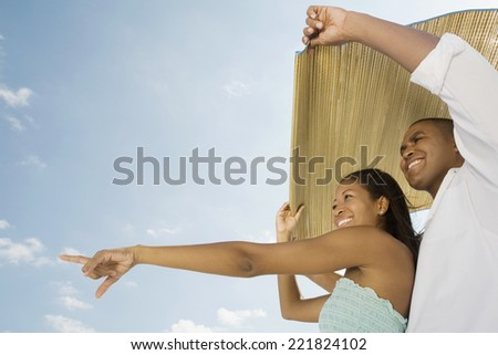 African couple holding mat in wind - stock photo