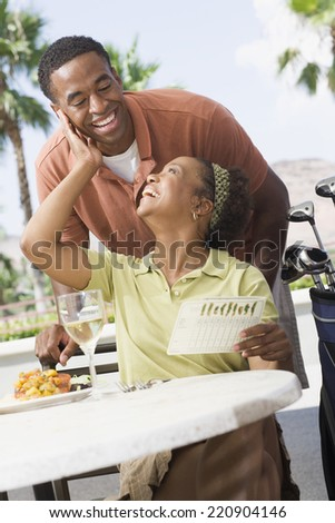 African couple smiling at each other at restaurant - stock photo