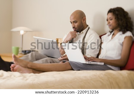 African couple typing on laptops - stock photo