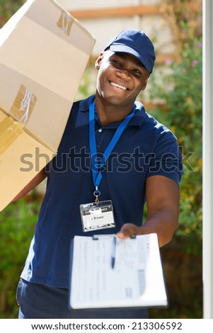 african delivery man carrying parcel and presenting receiving form - stock photo