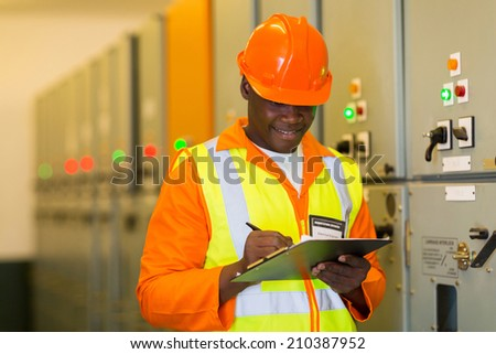 african electrical engineer in substation control room - stock photo