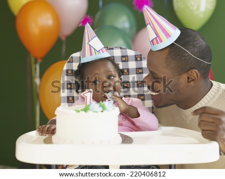 African father and baby in high chair eating birthday cake - stock photo