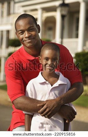 African father and son hugging outdoors - stock photo