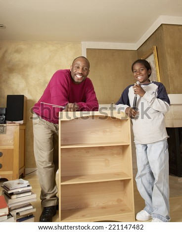 African Father And Son Putting Furniture Together
