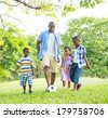 African Father Playing Ball with Children in Park - stock photo