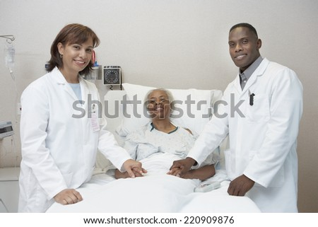 African female and male doctors holding hands with senior patient in hospital bed - stock photo