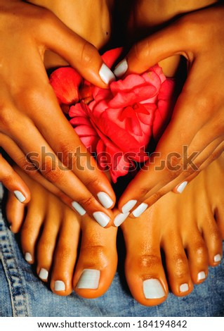 african Female feet and hand, blue pedicure with pink flower - stock photo