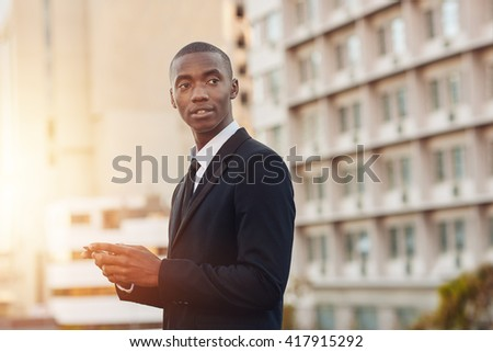 African finance entrepreneur standing in a city with mobile phone
