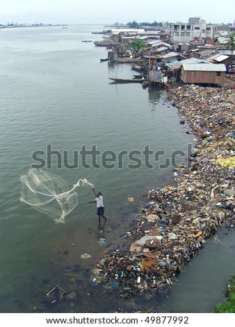 African fisherman casting his net surrounded by rubbish - stock photo