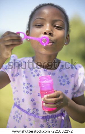African girl blowing bubbles - stock photo
