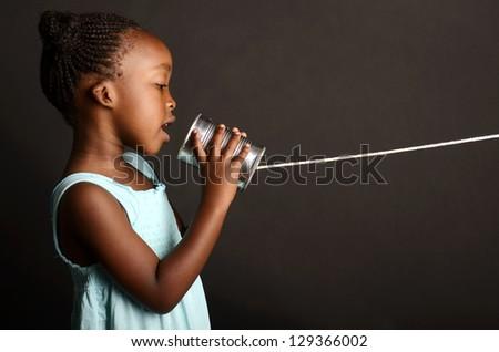 African girl communicating through a tin - stock photo