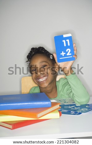 African girl holding addition flash cards - stock photo