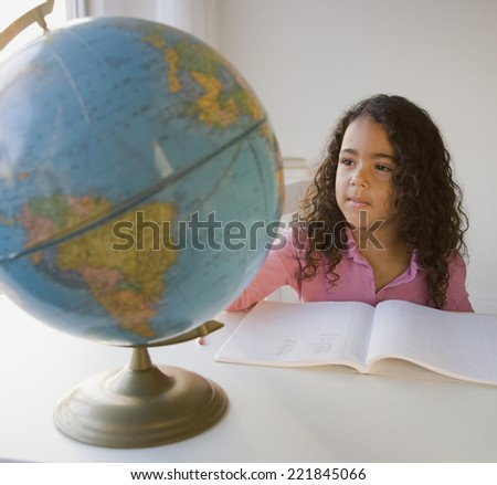 African girl looking at globe - stock photo