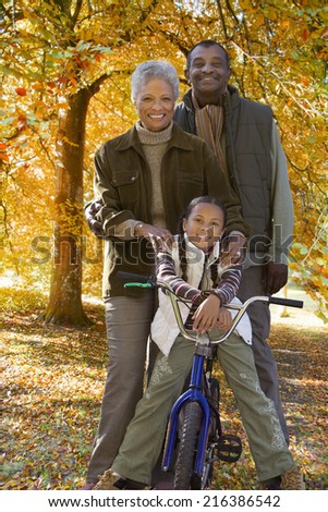 African girl on bicycle with grandparents in autumn - stock photo