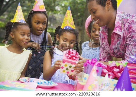 African girl receiving gift at birthday party - stock photo