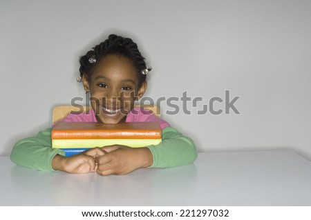 African girl with stack of school books - stock photo