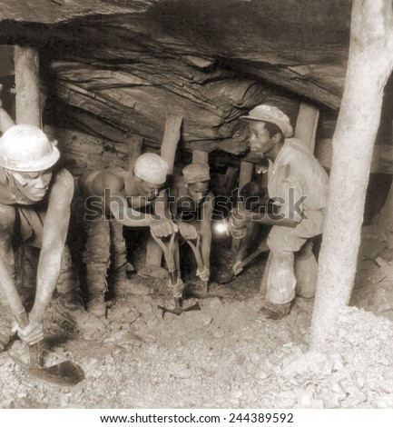 African gold miners developing a drift, a tunnel following a vein of ore, in the Crown Mine, in the greatest gold bearing region of the world, near Johannesburg, South Africa. 1935. - stock photo