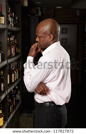 African guy in a wine shop examining shelves - stock photo