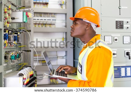 african industrial electrician working in power plant control panel - stock photo