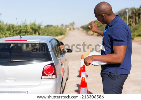 african instructor teaching learner driver to park a car in testing ground - stock photo