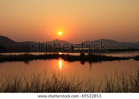 African lake at sunrise with the light reflecting off the calm water