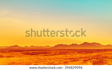 African landscape in bright colors - hot climate in stone desert with silhouettes of hills on the horizon. Safari in Sahara desert - exotic adventure and extreme travel in Arabian desert. - stock photo