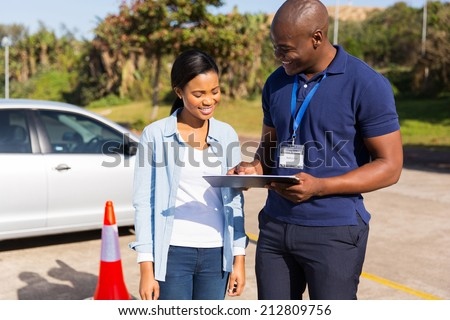 african learner driver with instructor before talking driving test - stock photo