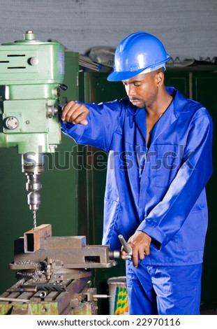 African machinist operating a drilling machine