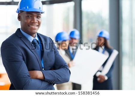 african male construction manager with arms folded - stock photo
