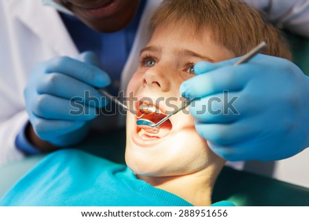 african male dentist examining little boy teeth close up - stock photo