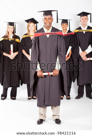 african male graduate with classmates at graduation - stock photo