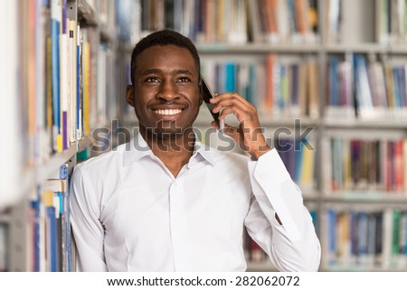 African Male Student Talking On The Phone In Library - Shallow Depth Of Field - stock photo