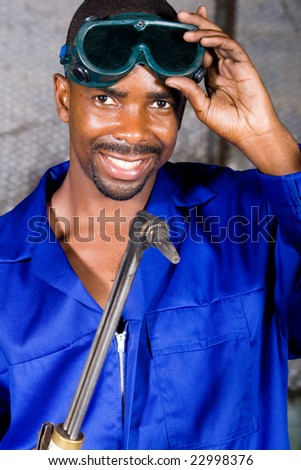 african male welder with protective goggles and gas welding machine - stock photo