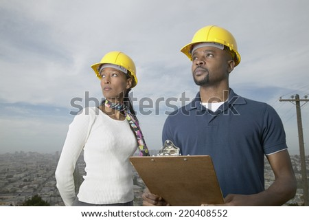 African man and woman with hard hats and clipboard - stock photo