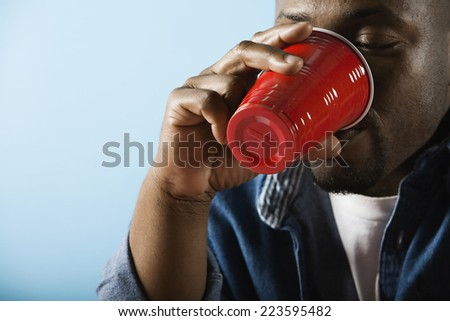 African man drinking from plastic cup - stock photo