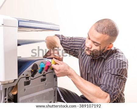 african man fixing photo copier - stock photo