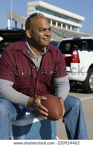 African man holding football at tailgate party