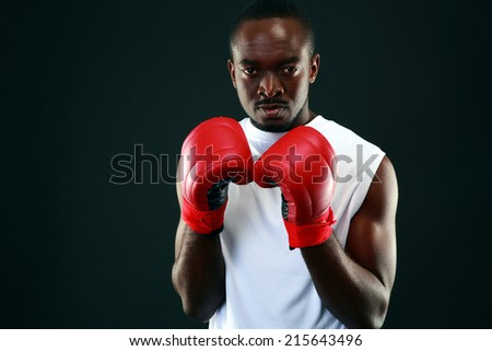 African man in boxing gloves standing over black background - stock photo
