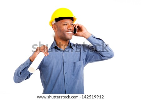 African man in hard hat talking on his mobile phone holding building plans isolated on white - stock photo
