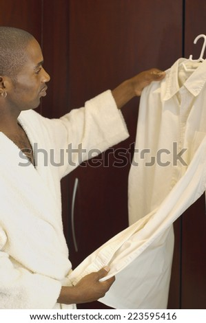 African man looking at shirt on hanger - stock photo