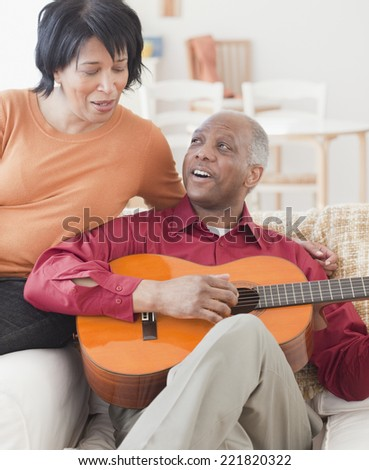 African man playing guitar for wife - stock photo