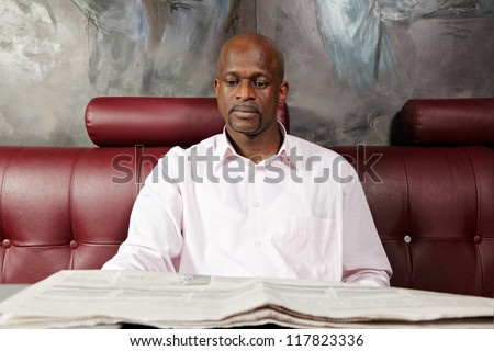 African man reading paper while sitting on red leather sofa - stock photo