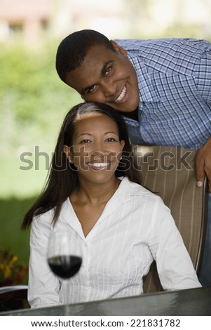 African man resting chin on wife's head