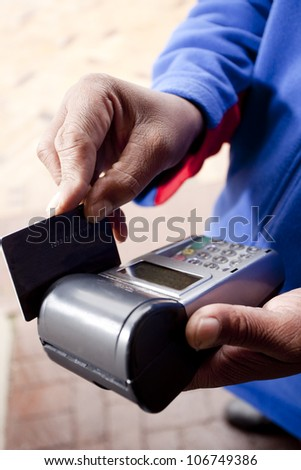 African man's hand, swiping a credit card through a wireless credit card terminal in a fuel station's forecourt. - stock photo