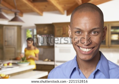 African man smiling with wife in background