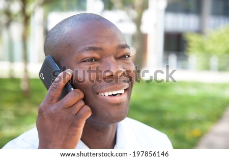 African man talking at phone outside in a park - stock photo