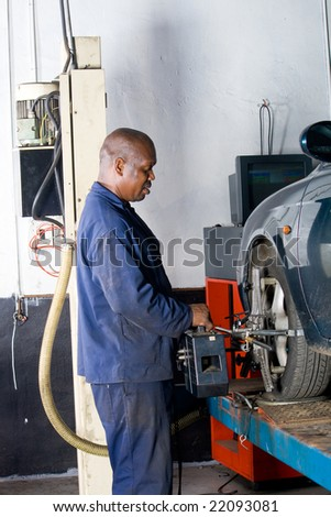 african mechanic working on a vehicle wheel alignment - stock photo