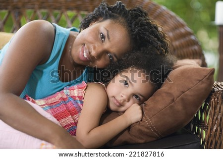 African mother and daughter laying on sofa - stock photo