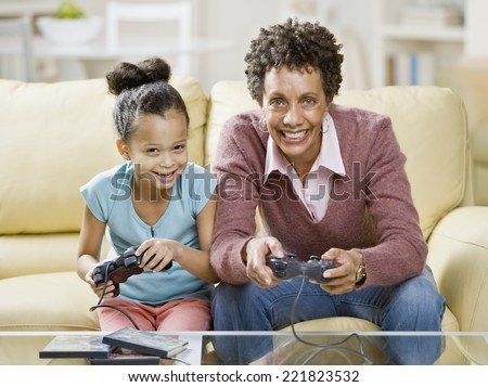 African mother and daughter playing video games - stock photo