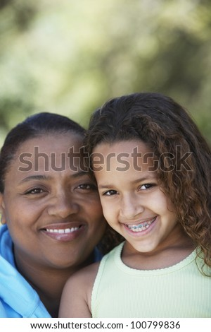 African mother and daughter with braces smiling - stock photo